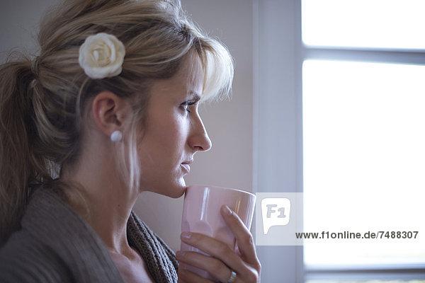 Junge Frau am Fenster stehend mit Kaffee