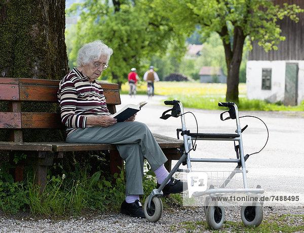 Österreich  Seniorin sitzend auf Bank und Lesebuch