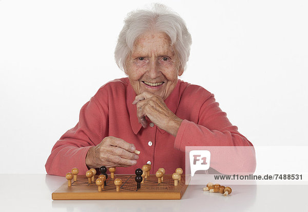 Portrait of senior woman playing Fox And Hen Game  smiling