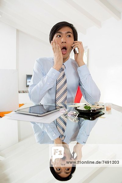 Young Asian businessman talking on his smartphone