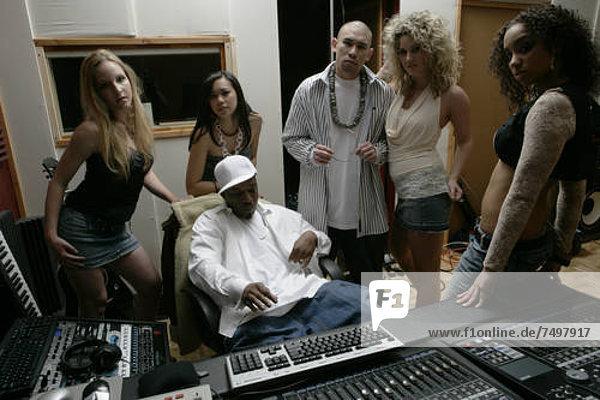 .Eine Gruppe von Menschen werden zusammen in einem Tonstudio gesehen.