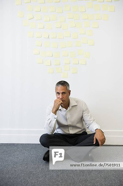 Businessman sitting behind wall covered in sticky notes