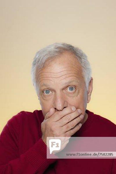 Studio shot of senior man covering lips
