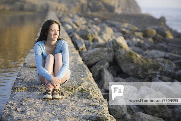 sitzend  Wasser  Steinmauer  Frau
