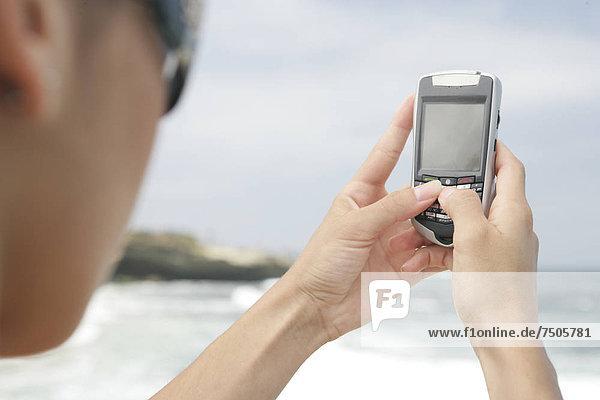 Blick auf eine Frau hält einen Handy.