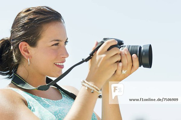 Portrait of young woman taking pictures with camera