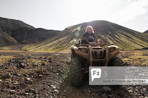 Porträt einer mittleren erwachsenen Frau  die auf einem Fahrzeug gegen die Bergkette sitzt  Island