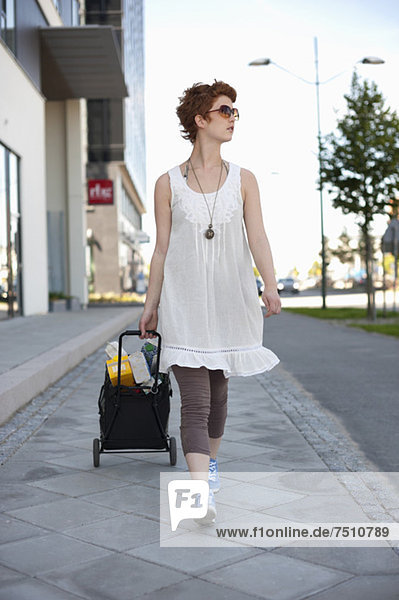 Full length of young woman with shopping bag walking on sidewalk