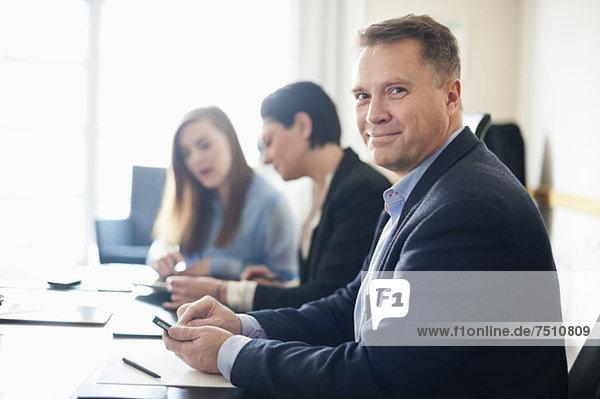 Porträt eines reifen Geschäftsmannes  der mit Kolleginnen am Schreibtisch sitzt.