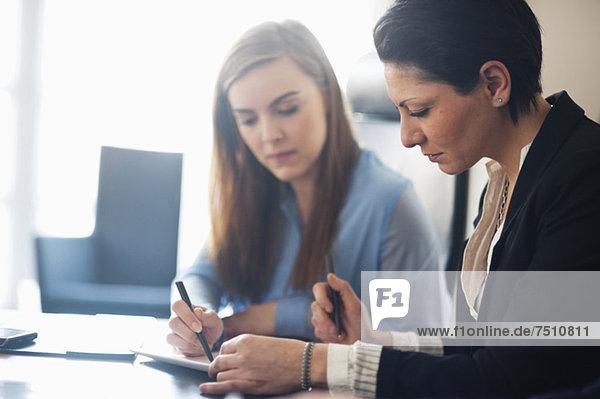 Zwei Geschäftsfrauen arbeiten am Schreibtisch im Büro