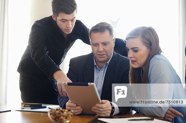 Geschäftsleute  die ein digitales Tablett im Meeting verwenden