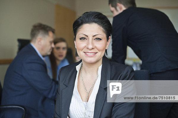 Porträt einer mittleren erwachsenen Geschäftsfrau  die in der Versammlung gegen Menschen sitzt.