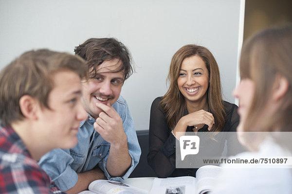Gruppe von Studenten diskutieren während des Studiums im Klassenzimmer