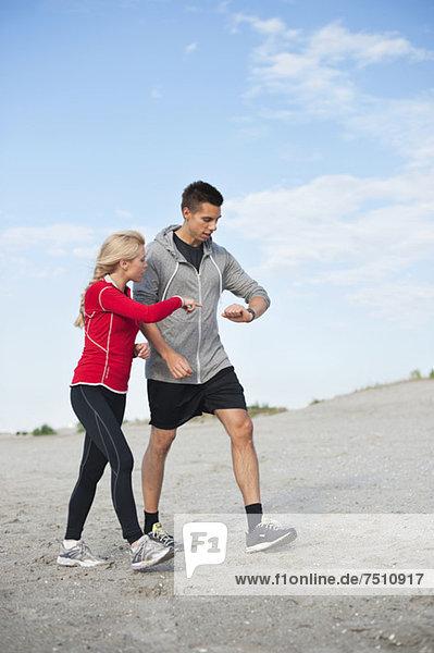 Junge Jogger beim Auschecken am Strand