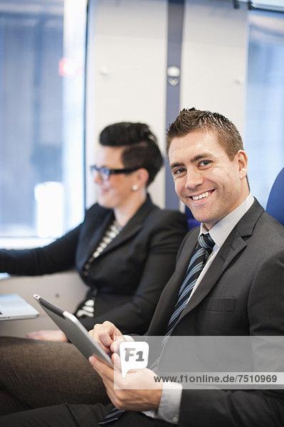 Portrait eines glücklichen Geschäftsmannes mit digitalem Tablett und Geschäftsfrau im Hintergrund