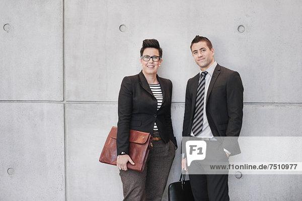 Porträt von glücklichen Geschäftsleuten  die Taschen an der Wand halten