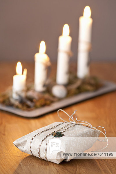 Sealed gift with lit candles on wooden table