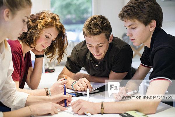 Junge Studenten  die gemeinsam am Tisch studieren