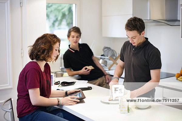 Junges Mädchen mit digitalem Tablett und männlichen Freunden an der Küchentheke
