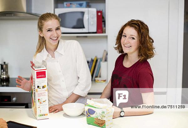 Porträt von glücklichen Freundinnen  die zusammen an der Küchentheke stehen