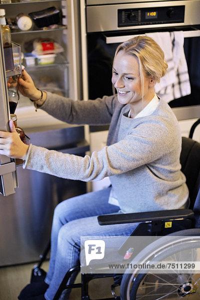 Glückliche behinderte Frau im Rollstuhl beim Herausnehmen der Flasche aus dem Kühlschrank in der Küche