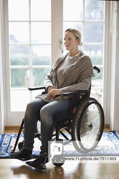 Nachdenkliche behinderte Frau  die im Rollstuhl zu Hause wegschaut.