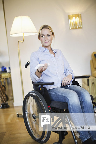 Behinderte Frau im Rollstuhl mit Fernbedienung