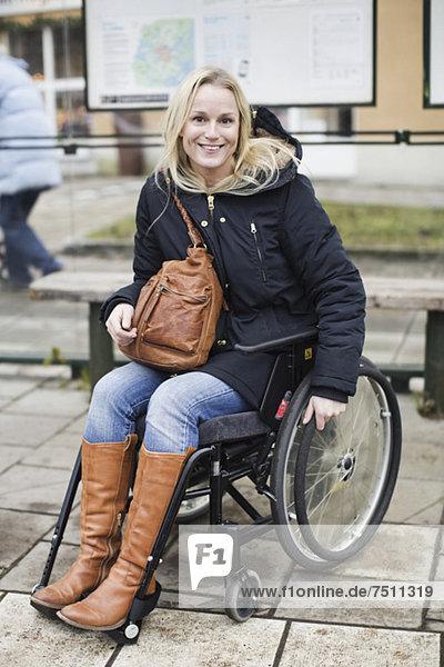 Porträt der glücklichen behinderten Frau im Rollstuhl an der Bushaltestelle