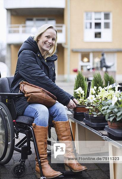 Porträt einer behinderten Frau im Rollstuhl bei der Pflanzenwahl in der Gärtnerei