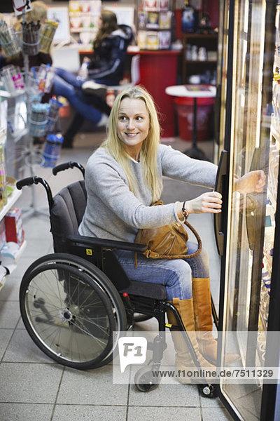 Glückliche behinderte Frau im Rollstuhl im Kühlbereich des Supermarktes schaut weg