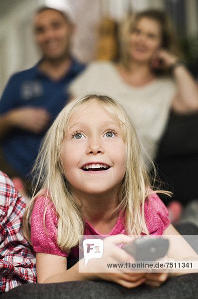 Kleines Mädchen mit Fernbedienung beim Fernsehen und im Hintergrund sitzende Eltern