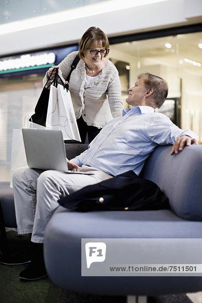 Senior Mann mit Laptop  der Frau mit Einkaufstaschen im Einkaufszentrum ansieht
