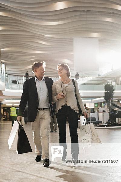 Glückliches Seniorenpaar mit Taschen im Einkaufszentrum