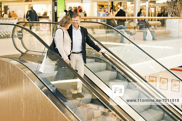 Glückliches Seniorenpaar auf einer Rolltreppe im Einkaufszentrum