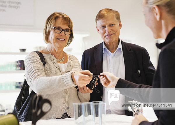 Glückliches Senior-Paar übergibt Kreditkarte an Verkäuferin im Geschäft