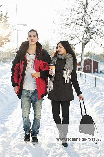 Junge Freunde  die auf einer verschneiten Straße spazieren gehen.