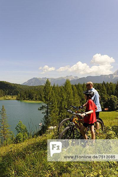 Cycling tour with mountain bikes  father and son in front of Lake Lautersee  Mittenwald  Karwendel Mountains  Werdenfelser Land  Upper Bavaria  Bavaria  Germany  Europe