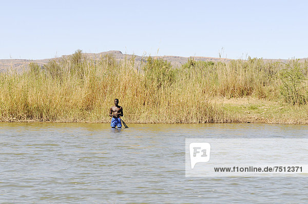 Fisherman standing in the Oranje  Orange River  border river between Namibia and South Africa