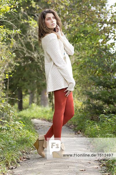 Junge Frau mit langem weißem Pullover und roter Strumpfhose  Outdoor