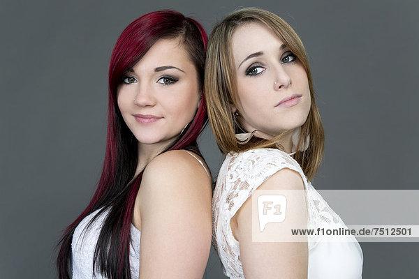 Zwei junge Frauen Rücken an Rücken  Portrait