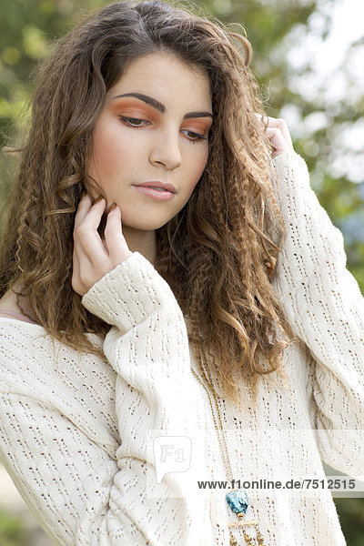 Young woman wearing a white sweater  outdoors