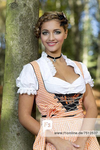 Junge lächelnde Frau im Dirndl posiert an Baum  Portrait  Dirndllook