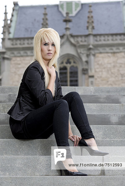 Young woman with long blonde hair wearing a black jacket and pants posing on stone steps