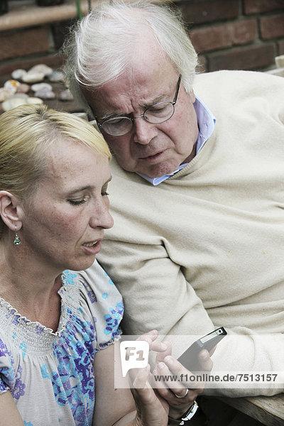 Junge Frau erklärt Senior Smartphone