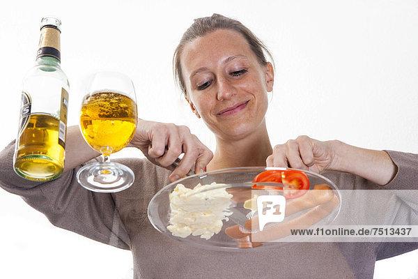 Junge Frau sitzt an einem Glastisch und isst Bockwürstchen  Frankfurter  mit Kartoffelsalat  Senf und einem Pils Bier