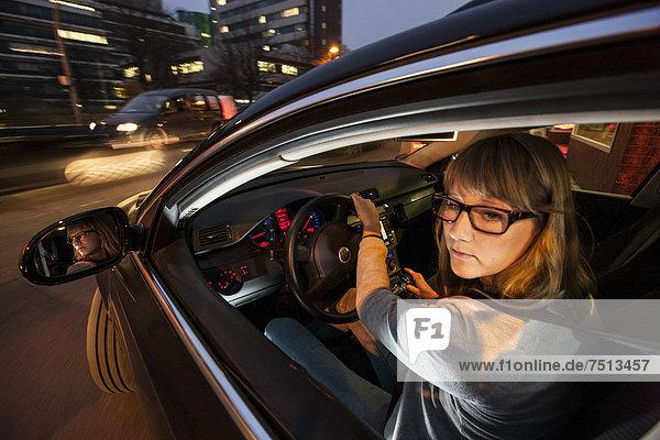 Junge Frau fährt Auto  in der Innenstadt  abends