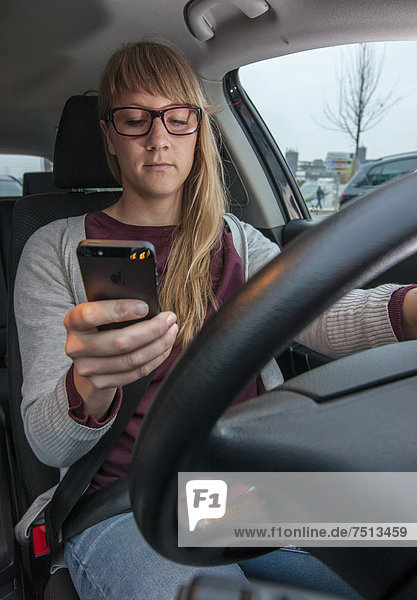 Junge Frau fährt Auto  bedient die Tastatur von ihrem Handy während der Fahrt