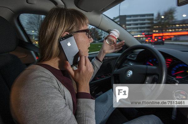 Junge Frau fährt Auto in der Innenstadt  telefoniert mit dem Handy während der Fahrt  hält gleichzeitig einen Kaffeebecher fest