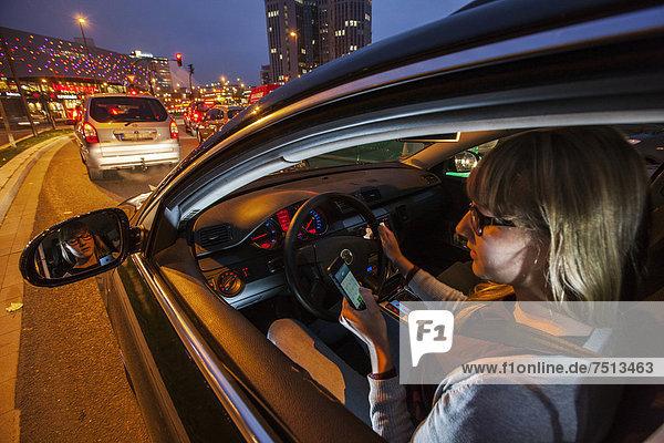 Junge Frau fährt Auto in der Innenstadt  abends  bedient die Tastatur von ihrem Handy während der Fahrt