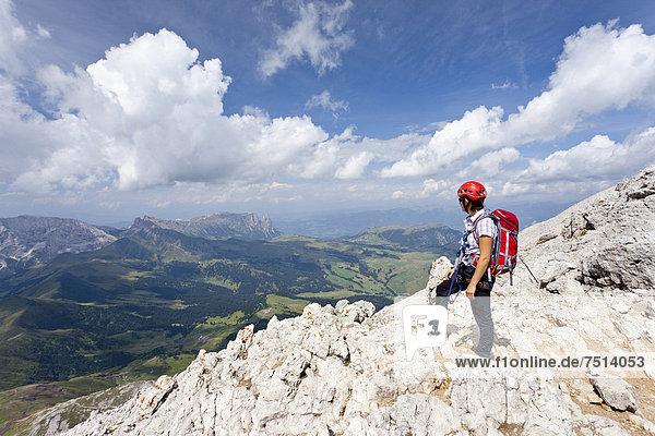 Bergsteiger auf dem Gipfelgrat beim Aufstieg zum Gipfel des Plattkofel über den Oskar Schuster Stieg  Klettersteig  hinten der Schlern  Dolomiten  Südtirol  Italien  Europa